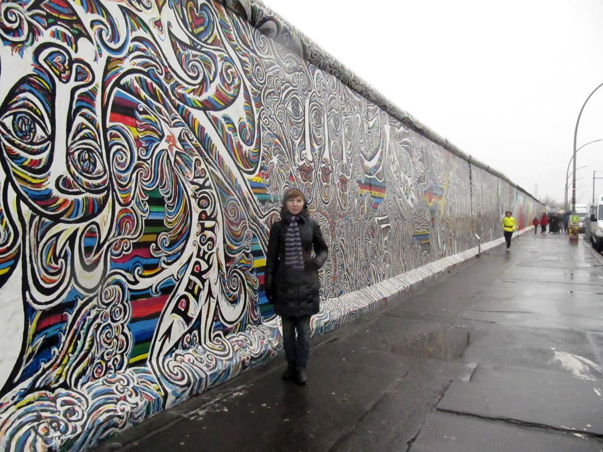 на фоне Берлинской стены